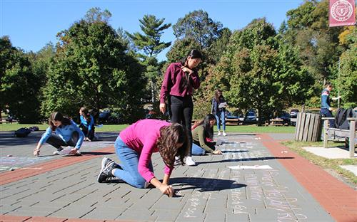 Student using chalk to write sonnets on the ground in the front of the High School walkway.