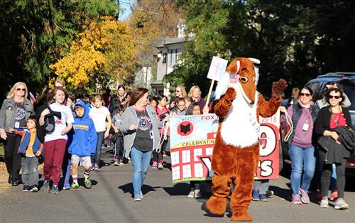Students and teachers walking with fox mascot for 90th anniversary parade
