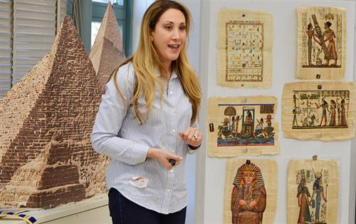 Marisa Horowitz-Jaffe stands in front of a large pyramid statue and images of ancient artifacts.